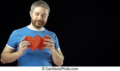 Happy man in blue tshirt holds two red heart shapes. Love, romance, dating, relationship concepts. Black background. 4K video