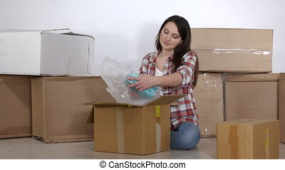 Woman sitting on the floor in a new apartment unpacks the...