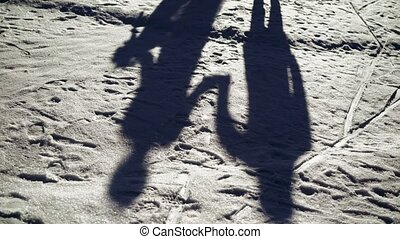 Young couple dancing at winter park at sunny day shadow