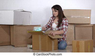 Woman moving in a new apartment packing cardboard boxes
