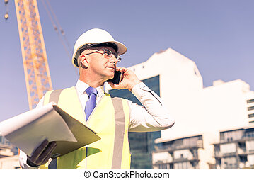 Man architector outdoor at construction area having mobile...