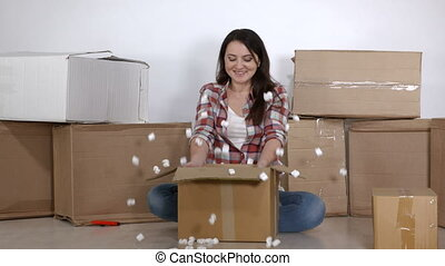 Happy woman unpacks moving cardboard boxes in a new apartment