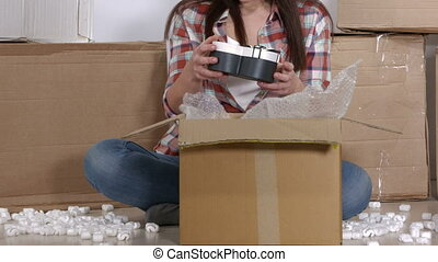 Woman unpacks moving cardboard boxes in new apartment pulls...