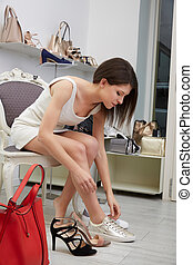 female feet that is tried on the shoes in shop
