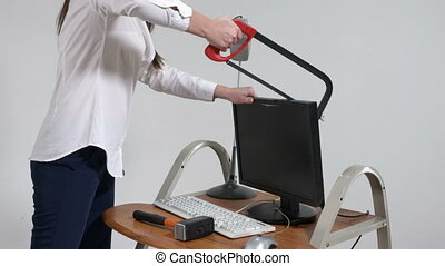 Crazy office worker destroying desktop computer with hacksaw...
