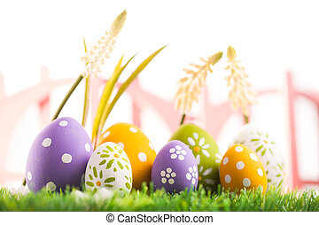 Row of Easter eggs on grass with a white background