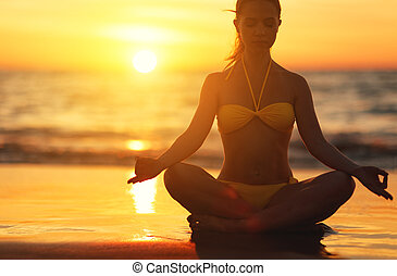 woman practices yoga and meditates in lotus position on...