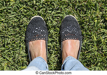selfie suntanned female feet on green grass