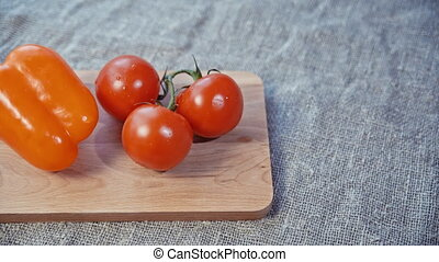 tomatoes, bell pepper lying on a wooden Board. slow motion