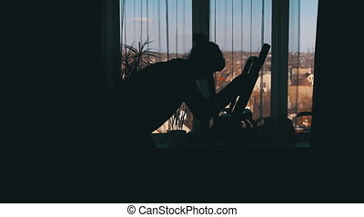 Silhouette of the Girl Exercisingon the Elliptical Trainer Cross Trainer at Home on Against the Window.