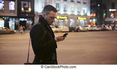 Young man talking on the phone outdoor at night in city