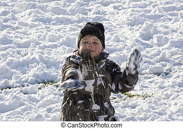 Young boy throwing snowball