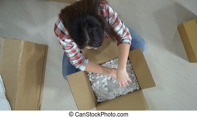 woman unpacking moving cardboard box or parcel contains a...