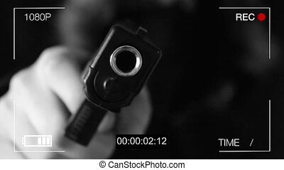 the young man points the gun at the hidden camera,black background