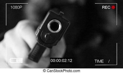 the young man points the gun at the hidden camera,black...