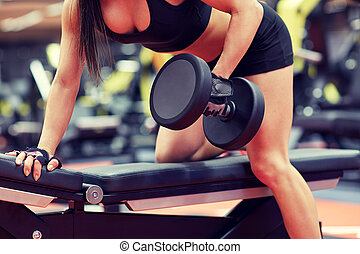 woman flexing muscles with dumbbell in gym - sport, fitness,...