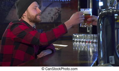 Guy takes beer at the pub - Attractive bearded guy taking...