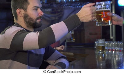 Guy smells beer at the pub - Attractive bearded guy smelling...
