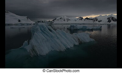 Iceberg in sunrise in Antarctica - View of mountains in...