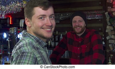 Man shows a glass of beer at the pub