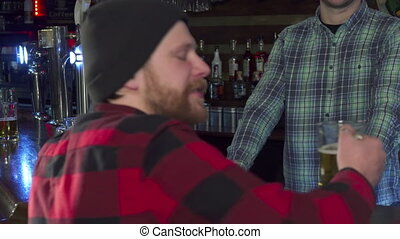 Guy turns back with glass of beer - Attractive bearded guy...