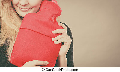 Woman holding warm red hot water bottle - Smiling calmly...