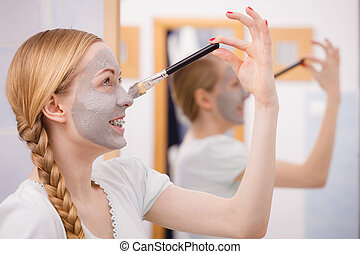 Happy young woman applying mud mask on nose - Facial dry...