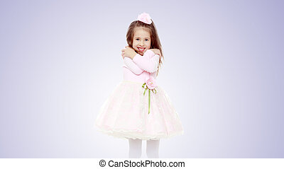 Elegant little girl in a pink dress.