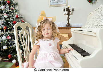 Little girl plays music on the piano. - Beautiful, chubby...
