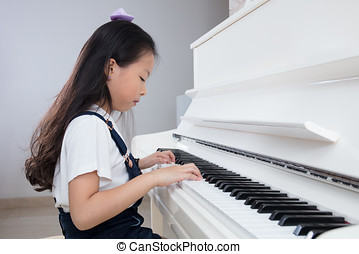 Asian Chinese little girl playing classical piano at home -...