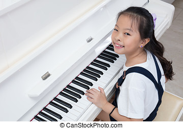 Happy Asian Chinese little girl playing classical piano at...