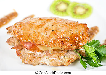 pork chop - Cooked pork chop with kiwi and parsley on a...