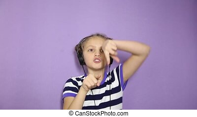 young girl with pigtails listening music on headphones and dancing