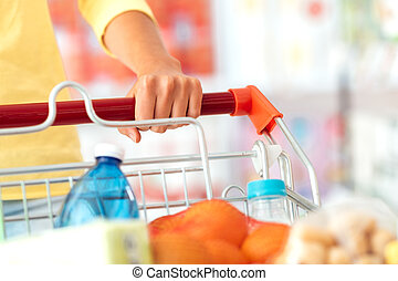 Shopping at the supermarket - Woman doing grocery shopping...