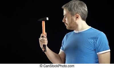 Handsome man in blue tshirt holds hammer. DIY, repair,...