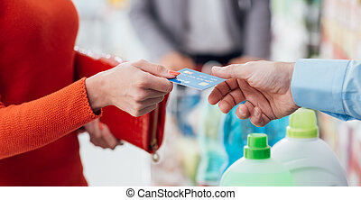 Woman at the checkout - Woman doing grocery shopping at the...