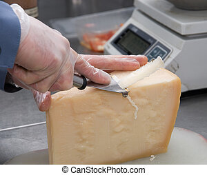 cutting cheese - Hand cutting a piece of cheese