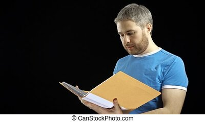 Handsome man in blue tshirt looking through papers in yellow folder. Cotract, bills, checklist concepts. Black background. 4K video