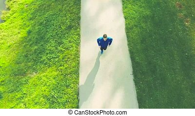 Young athlete running in green nature on asphalt path