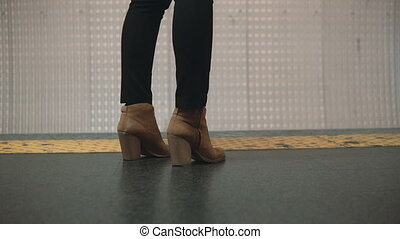 Close-up view of woman foot wearing shoes in subway platform. Girl standing near restrictive line and waiting train.