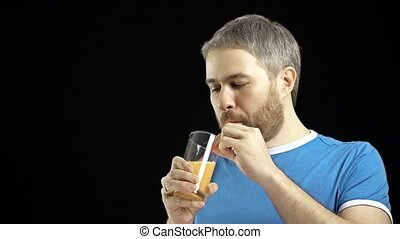Athletic bearded gray haired man in blue t-shirt drinking orange juice. Black background.