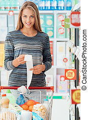 Happy woman with grocery receipt - Young smiling woman...
