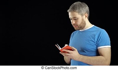 Handsome man in blue tshirt writing in his red notebook....