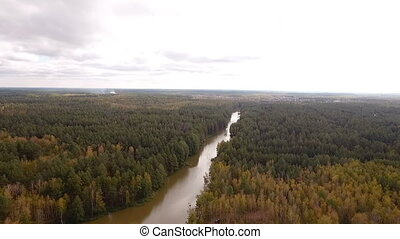 Aerial photography of the river flowing along the forest -...
