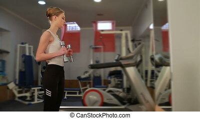 Young sports woman doing exercises with dumbbells in the gym. Fitness club workout