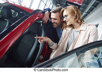 Adult couple admiring car in the showroom