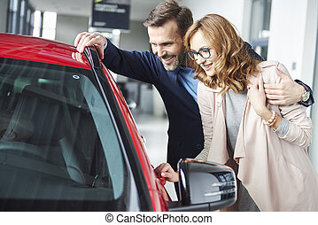 Waist up of couple next to red car