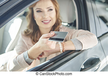 Woman sitting in a car with credit card