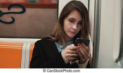Portrait of attractive girl in subway train using smartphone. Young woman chatting with friends and smiling.