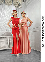 Two young, beautiful women in long, evening red and peach...